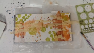 Step four:  The addition of some serpentine green while the orange is still wet, using a circle template to push the paint through to the page.